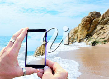 View over the mobile phone display during taking a picture of Costa Brava beach in Calella, Spain. Holding the mobile phone in hands and taking a photo. Focused on mobile phone screen.