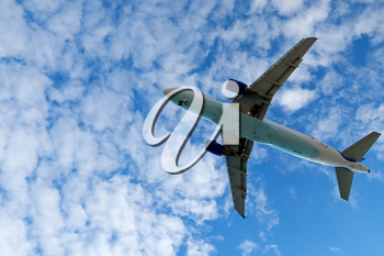 Jet airplane landing in bright cloudy sky