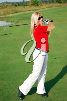 Blonde girl on golf field playing golf