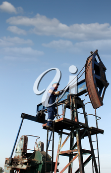 oil worker climbs up to the pump jack