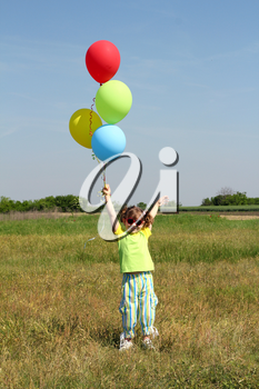 happy child with colorful balloons on field