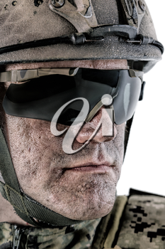 Close up studio shot of special forces soldier in field uniforms and combat helmet, portrait isolated on white background. Protective goggles glasses are on