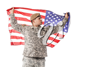 Army Ranger from Special Troops Battalion in universal Camouflage pattern Uniforms and Tan beret with Ranger Regiment crest standing and holding waving US flag in his hands proudly. National holidays: Veterans Day, Memorial Day