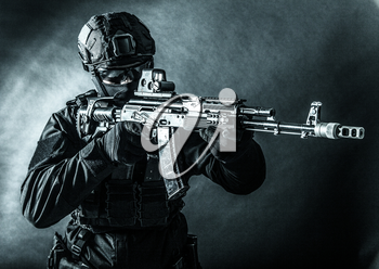 Police tactical team member, army special forces, private security company fighter in black uniform, helmet and mask aiming with collimator sight on assault rifle, toned in blue, low key studio shoot