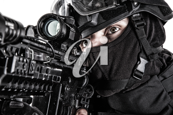 Close up studio portrait of police quick response group shooter in black uniform, searching target to shoot, observing area, aiming service rifle with optical sight close up portrait isolated on white