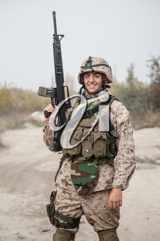 Smiling army soldier, United States Marine Corps infantry shooter in camo battle uniform, protected with body armor and helmet, posing with assault rifle in hands while standing near country road