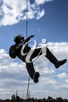 Special forces operator during assault rappeling with weapons