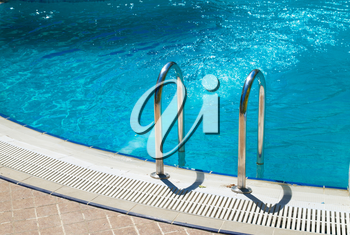 Swimming pool with stair and blue relaxing water