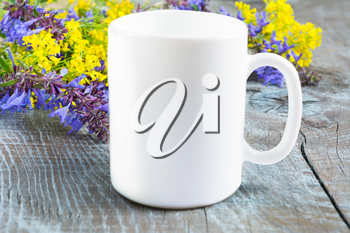 White coffee mug mockup with lilac and yellow flowers. Empty mug mockup with place for design or text. White coffee cup mockup.