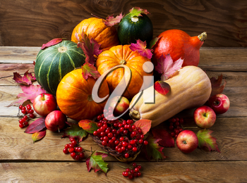 Abundant harvest concept with pumpkins, apples and berries. Thanksgiving background with seasonal vegetables and fruits. Fall background.