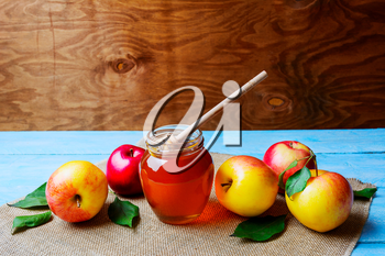 Honey glass jar and apples on rustic background copy space. Rosh hashanah concept. Jewesh new year symbols.