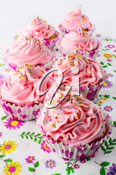 Pink birthday cupcakes  with whipped cream. Homemade cupcakes served for party. Birthday card background.