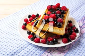 Soft Belgian waffles with blueberry, raspberry and blackcurrant. Breakfast waffles with fresh berries.