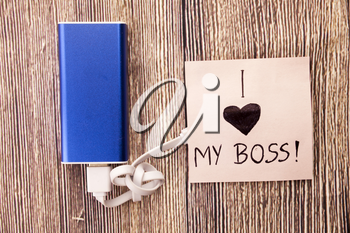 Power Bank with a piece of paper around, having words I Love my boss is present.Love for an officer, head or boss is mentioned in image. Business Concept is shown in picture.