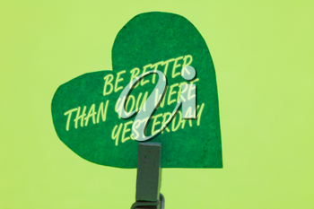 Conceptual hand writing showing Be Better Than You Were Yesterday. Business photo showcasing try to improve yourself everyday Clothespin holding green paper heart romantic message ideas
