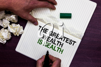 Text sign showing The Greatest Wealth Is Health. Conceptual photo being in good health is the prize Take care Man holding marker notebook page crumpled papers several tries mistakes