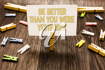 Text sign showing Be Better Than You Were Yesterday. Conceptual photo try to improve yourself everyday Clothespin holding white paper note several clothespins wooden floor