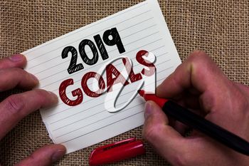 Writing note showing 2019 Goals. Business photo showcasing A plan to do for something new and better for the coming year Man's hand hold white paper with symbolic letter jute sack background