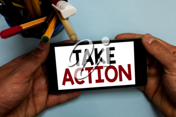 Conceptual hand writing showing Take Action. Business photo showcasing advices someone to do something or reaction right now Man holding cell phone looking messages apps cup markers