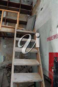 Steep wooden staircase crumbling attic and fire extinguisher sign in abandoned factory interior.
