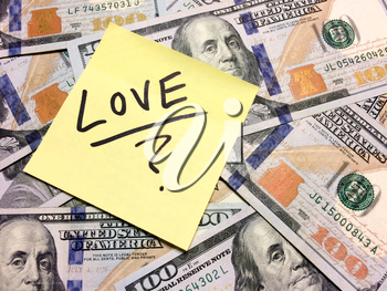 American cash money and yellow post it note with text Love with question mark in black color aerial view