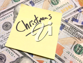 American cash money and yellow post it note with text Christmas in black color aerial view