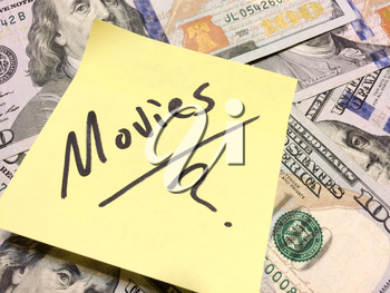 American cash money and yellow post it note with text Movies with question mark in black color aerial view