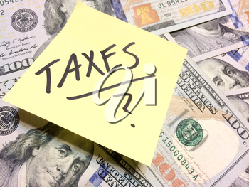 American cash money and yellow post it note with text Taxes with question mark in black color aerial view