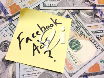 American cash money and yellow paper note with text Facebook Ads with question mark in black color aerial view