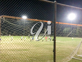Night time soccer game at playing field outdoor with people and kids