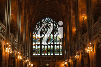 Manchester, UK: 20 October 2019: The John Rylands Library Historic Reading Room showing stained glass window and candelabra