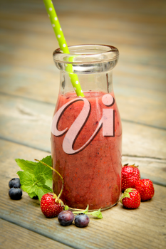 Berry smoothie with fresh fruits on a rustic wood