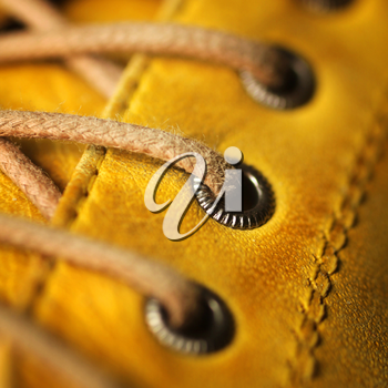 Close up of eyelet and lace on a leather yellow shoe.  Only the middle eyelet in focus.