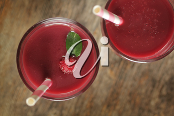 Top view of berry smoothies with a pink straw on a rustic background