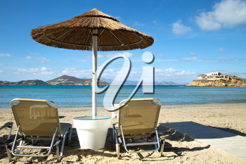 Sunbathing chairs on a beach with turquoise ocean and a straw parasol in Greece