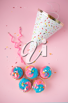 Top view of cupcakes with blue and pink icing, candles and birthday hat on a pink background