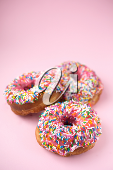 Three donuts with pink icing and candies on a pink pastel background