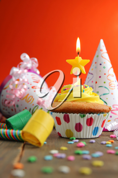 Vanilla cupcake with yellow frosting and a birthday candle with hats and blower on a wooden table and a orange background